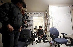 Ryan Bundy (L) and Wes Kjar, an occupier, take up positions after a door was rattled in an office at the Malheur National Wildlife Refuge near Burns, Oregon, January 6, 2016. REUTERS/Jim Urquhart