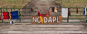 Signs left by protesters demonstrating against the Energy Transfer Partners Dakota Access oil pipeline sit at the gate of a construction access road where construction has been stopped for several weeks due to the protests near the Standing Rock Sioux reservation in Cannon Ball, North Dakota, U.S. September 6, 2016. REUTERS/Andrew Cullen